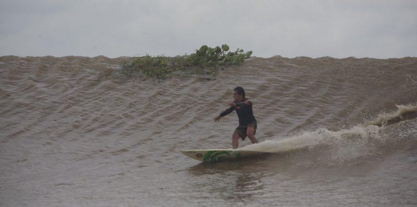 E até que enfim, depois de tanto tempo preso na espuma, Alberto Alves alcançou o rabo da onda em Mentawai, passando por plantas e galhos, Pororoca do Rio Araguari (AP). Foto: Toninho Jr..