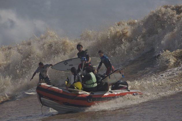 Serginho Laus, em pé no barco, espera a hora certa para pular, enquanto o australiano Skeet e outro não identificado a esquerda, se controlam na pressão da pororoca e das marolas deixadas pelo bote, Pororoca do Rio Araguari (AP). Foto: Bruno_Alves.