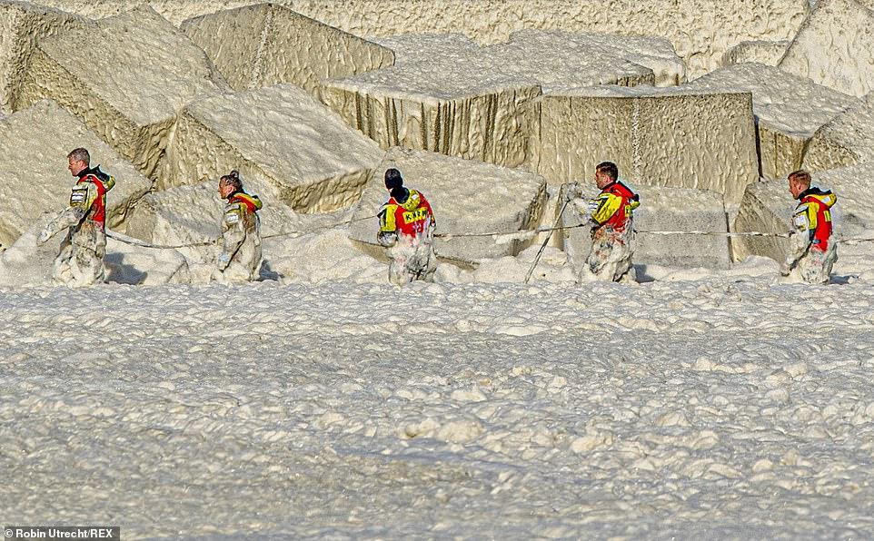 Equipe de resgate trabalha sobre forte camada de espuma na busca por sobreviventes.
