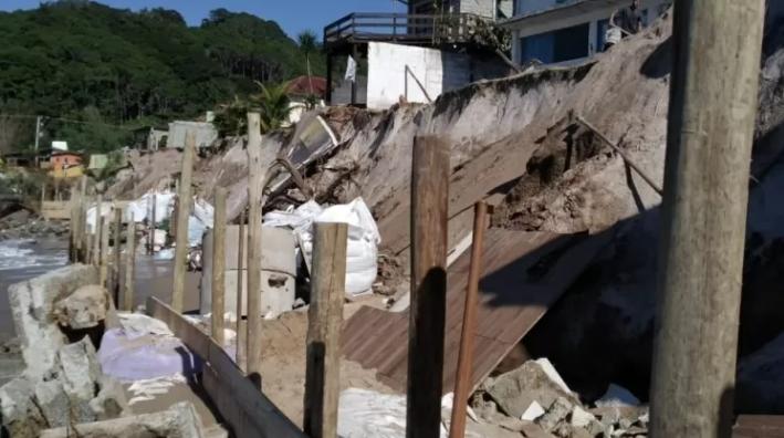 Moradores enchem sacos de areia para tentar conter o avanço do mar.