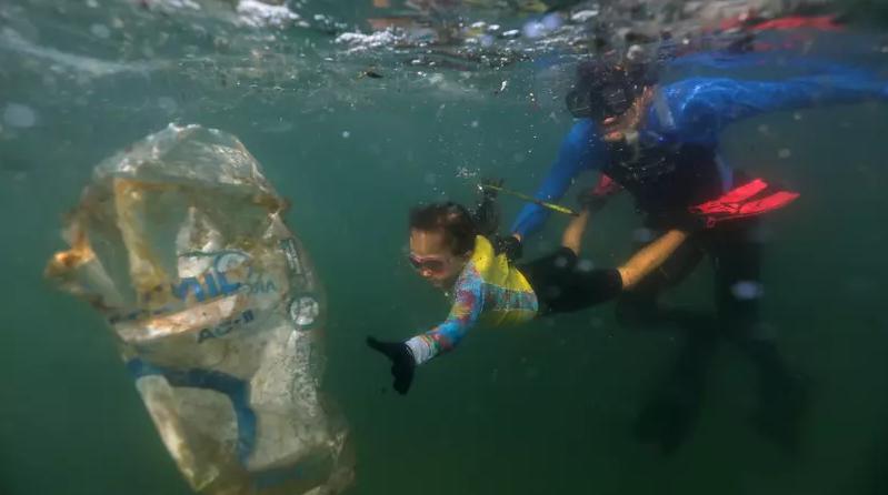 Nina recolhe lixo com o pai nas praias do Rio de Janeiro.