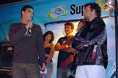 Léo Neves recebe das maõs de Teco Padaratz (à dir) o prêmio de campeão brasileiro do SuperSurf 2003. Foto: Ricardo Macario.