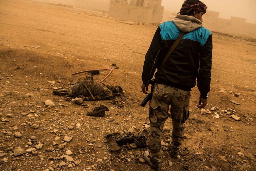 Soldado da ISOF (Forças de Operações Especiais do Iraque) durante a tempestade de areia, ao lado do corpo de um militante do ISIS, perto do front line em Mosul, Iraque
