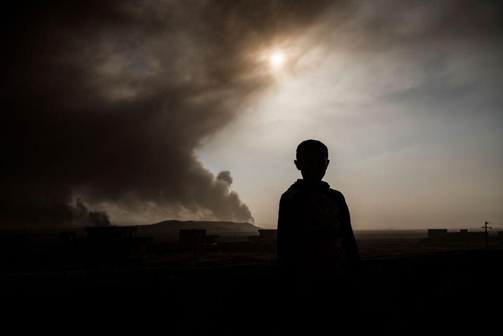 As crianças observam o fogo e a fumaça que sobem de poços de petróleo, incendiados pelos militantes do Estado Islâmico antes de fugirem da região produtora de petróleo em Qayyara, no Iraque, que foi recuperada pelas forças iraquianas, Iraque