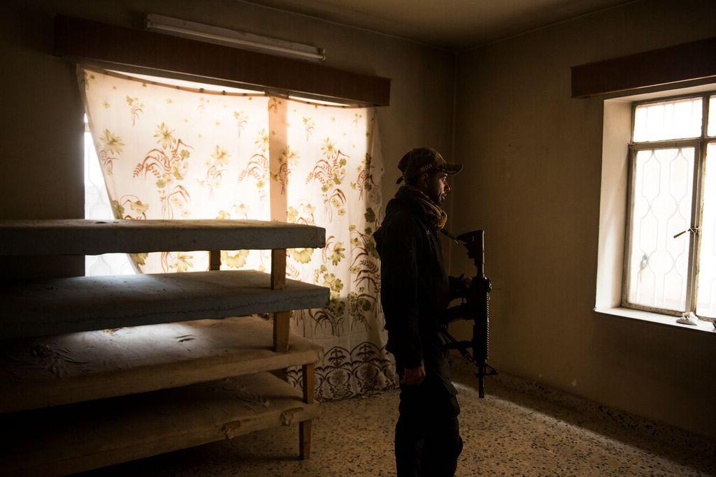 Soldado da ISOF (Forças de Operações Especiais do Iraque) escolhe uma casa abandonada para se posicionar no combate contra o Estado Islâmico, no oeste de Mosul. Iraque