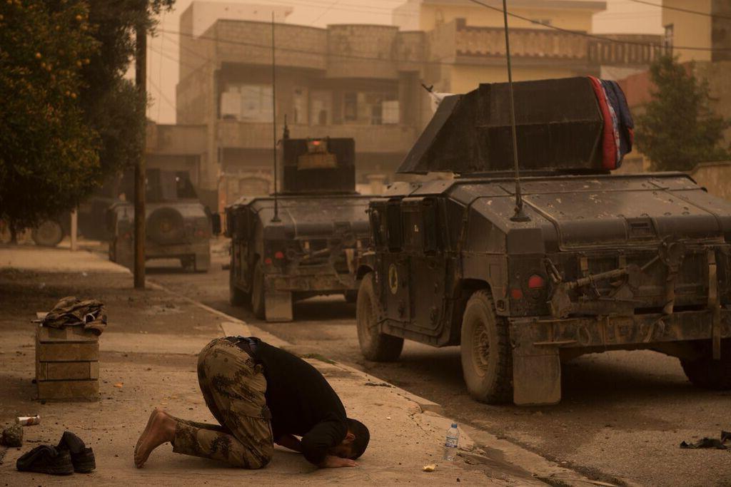 Soldado iraquiano reza durante batalha em Mosul, Iraque