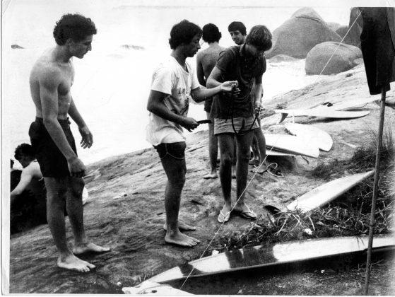 Durante o primeiro campeonato de surf na Trindade em 1977, Charlys Brown observa o Madureira entregando uma cordinha M&M, que ele fabricava a Roberto Moura, Trindade (RJ)